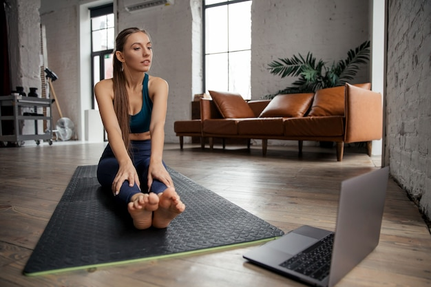 Young woman practicing online yoga, head to knee asana in living room. high quality photo