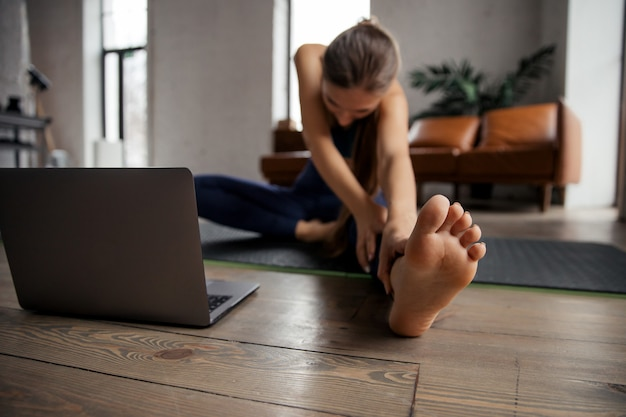 Young woman practicing online yoga, head to knee asana in living room. janu sirsasana pose. focus on foot.