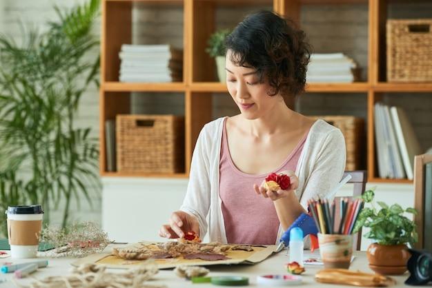 押し花などの植物素材を使ってオシバナアートを練習している若い女性...