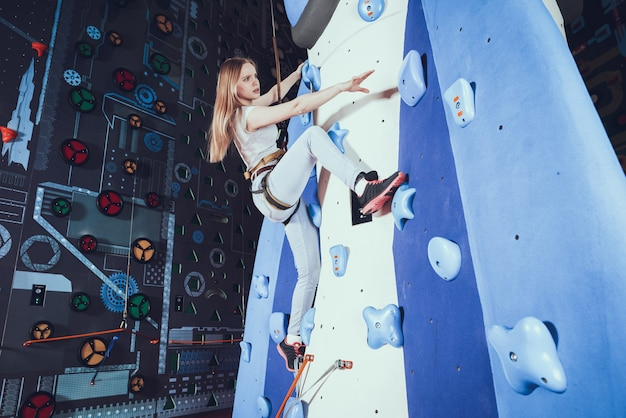 Young woman practicing rock climbing on rock wall indoors.