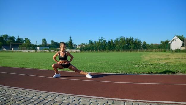 경기장에서 측면 돌진을 연습하는 젊은 여자