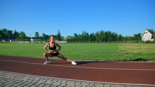 Young woman practicing side lunges at stadium