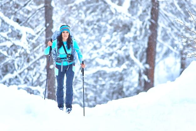 숲에서 폭설 중 스키 투어를 연습하는 젊은 여자
