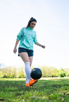 Young woman practicing soccer skills with ball