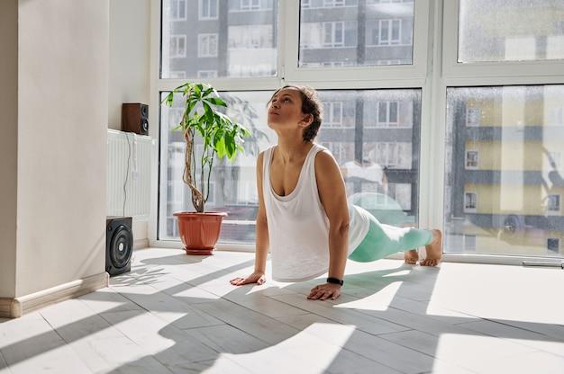 Young woman practicing urdhva mukha svanasana yoga pose