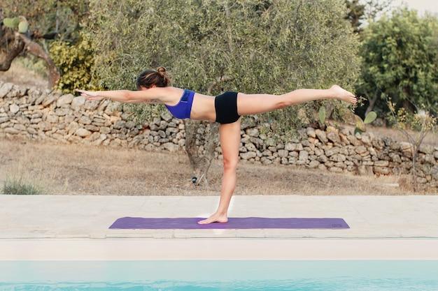 전사 iii 요가 연습하는 젊은 여자는 수영장 근처 포즈