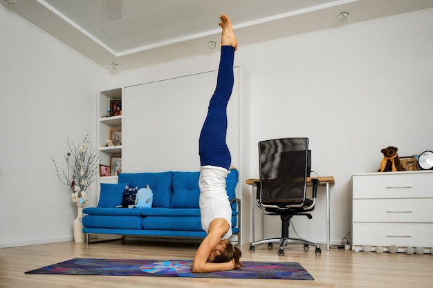 自宅でヨガを練習している若い女性は、サポートされている倒立で立っています