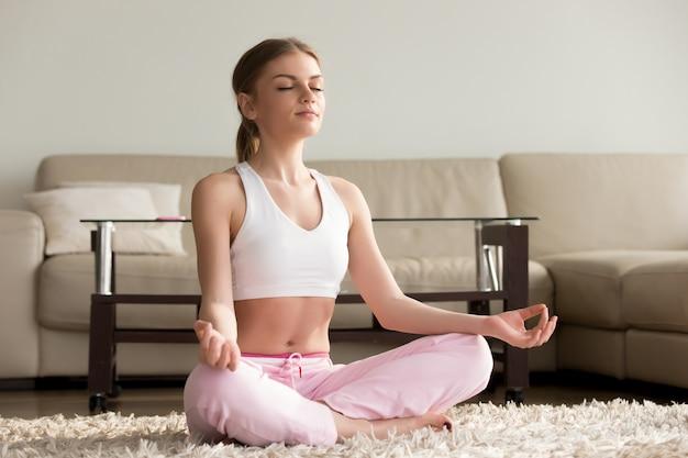 집에서 요가 연습하는 젊은 여자.