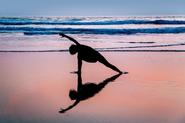 Young woman practicing yoga on beach in agonda, goa, india