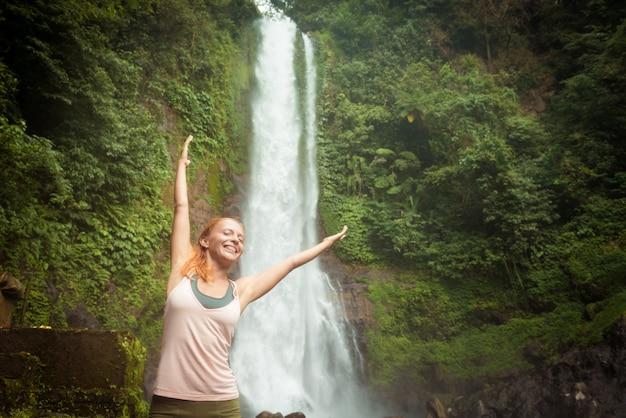 Giovane donna che pratica lo yoga dalla cascata