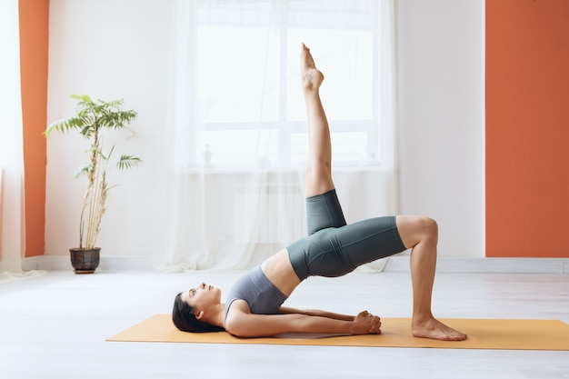 Young woman practicing yoga doing dvipada pithasana with leg extended upward half bridge pose