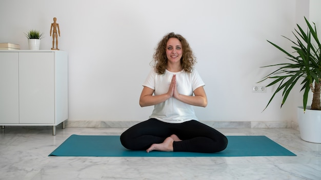 Young woman practicing yoga and doing the namaste salute on a blue mat at home