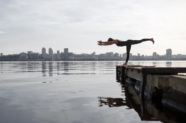 Тренировка йоги молодой женщины практикуя на тихой деревянной пристани с предпосылкой города. спорт и отдых в суете города