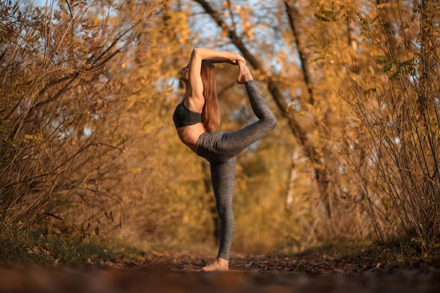 Young woman practicing yoga exercise at autumn park with yellow leaves.