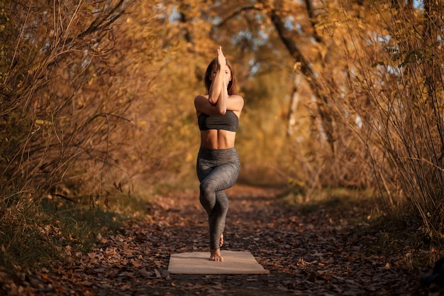 Young woman practicing yoga exercise at autumn park with yellow leaves