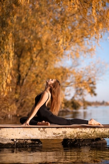 Young woman practicing yoga exercise at quiet pier in autumn park