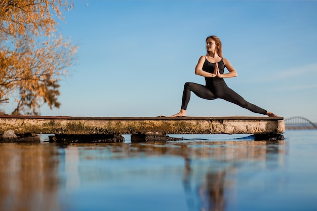 Young woman practicing yoga exercise at quiet wooden pier with city background. sport and recreation in city rush