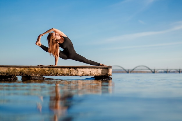 Young woman practicing yoga exercise at quiet wooden pier with city . sport and recreation in city rush