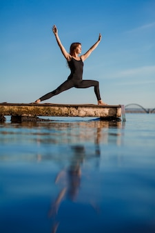 Young woman practicing yoga exercise at quiet wooden pier