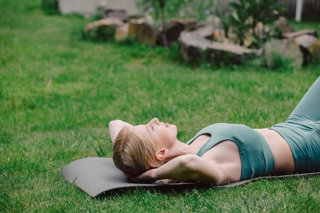 Young woman practicing yoga on the grass in the garden