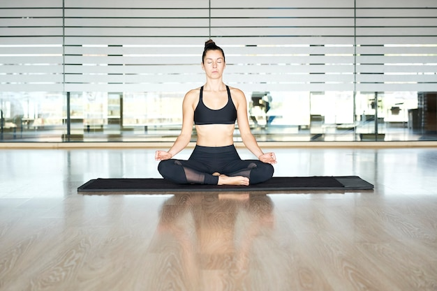 Young woman practicing yoga in a gym, exercising in black sportswear, doing meditation exercises.