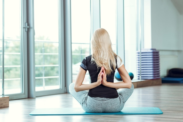 Young woman practicing yoga in gym. girl joining hands behind back