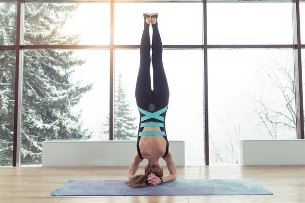 Young woman practicing yoga headstand pose, close-up on head