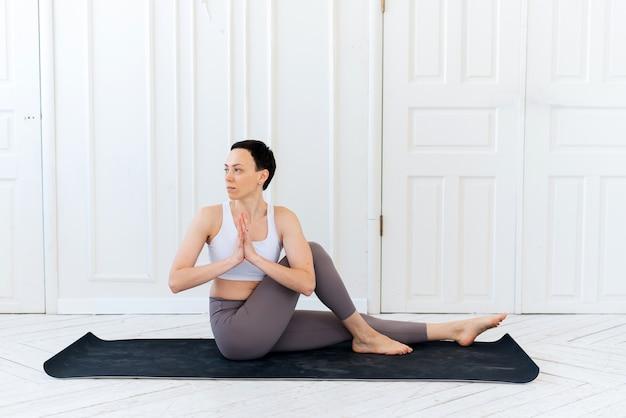 明るい背景でヨガを練習している若い女性。健康的なライフスタイルのコンセプト。