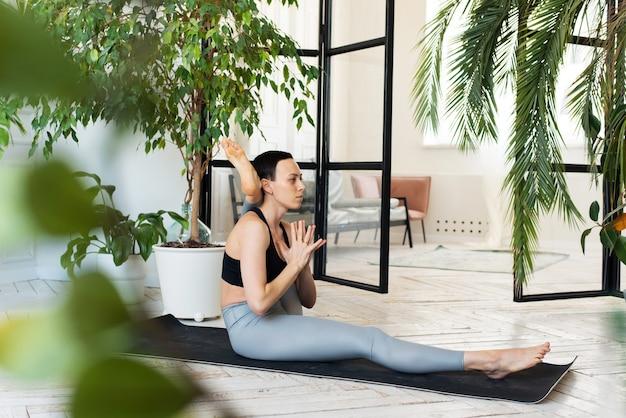 Молодая женщина упражнениями йоги на светлом фоне. концепция здорового образа жизни.