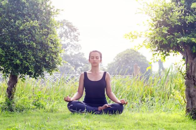 공원에서 요가 연습하는 젊은 여자