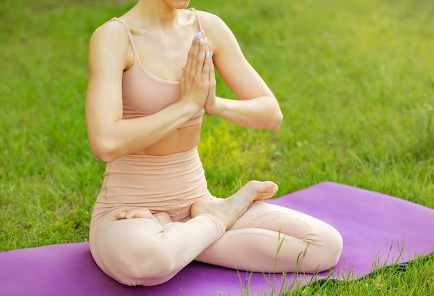 Молодая женщина практикует йогу утром, сидя прямо и удобно на коврике для йоги