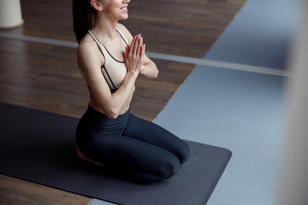ジムでマットの上に座っている間、祈りの位置でヨガを練習している若い女性。リラクゼーションと瞑想の概念。