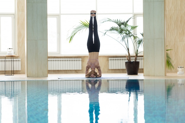 Young woman practicing yoga indoor in thermal zone of swimming pool.