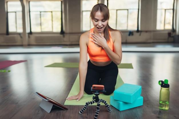 ヨガを練習している若い女性は、オンラインで先生と関わっています。