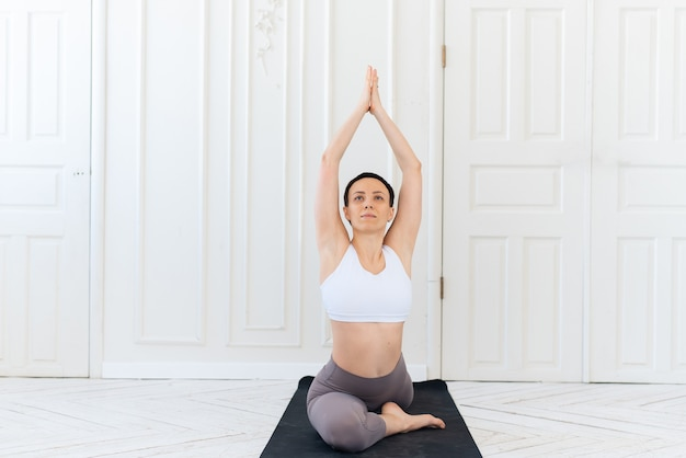 Young woman practicing yoga in a light background. healthy lifestyle concept.