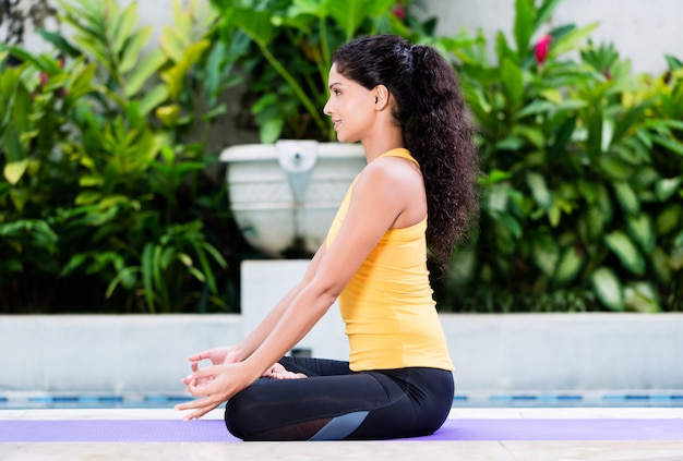 Young woman practicing yoga in lotus position outdoors