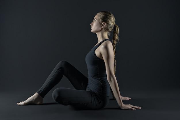 Молодая женщина упражнениями коврик йоги и леггинсы