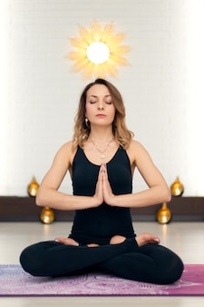Young woman practicing yoga meditation in gym