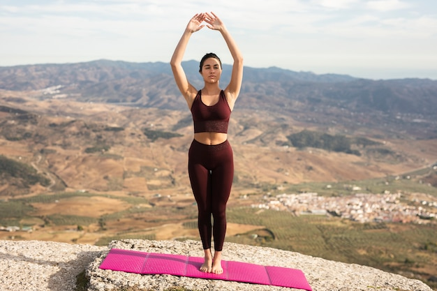 Young woman practicing yoga on mountain top