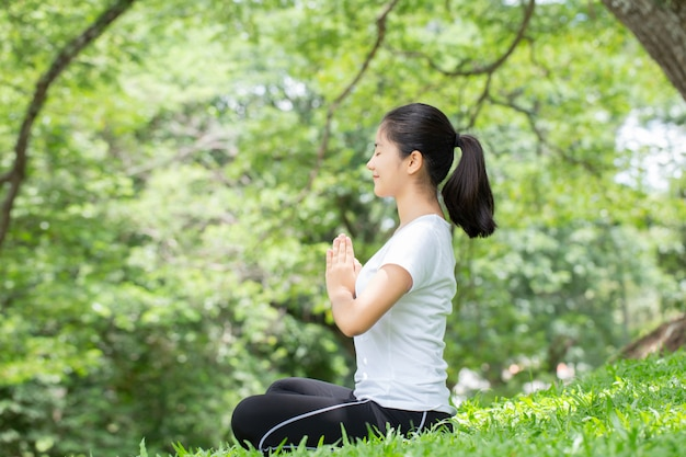 Young woman practicing yoga in the nature, asian woman is practicing yoga in city park