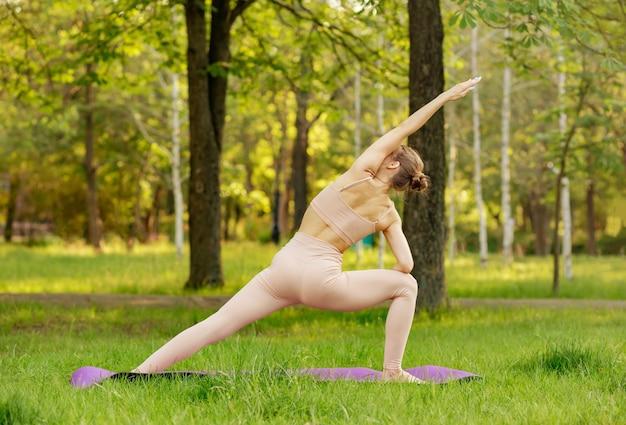 Молодая женщина упражнениями йоги на траве