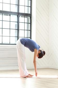Молодая женщина практикующих йогу на коврик для йоги
