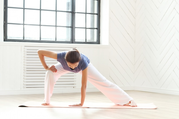 若い女性のヨガマットでヨガの練習