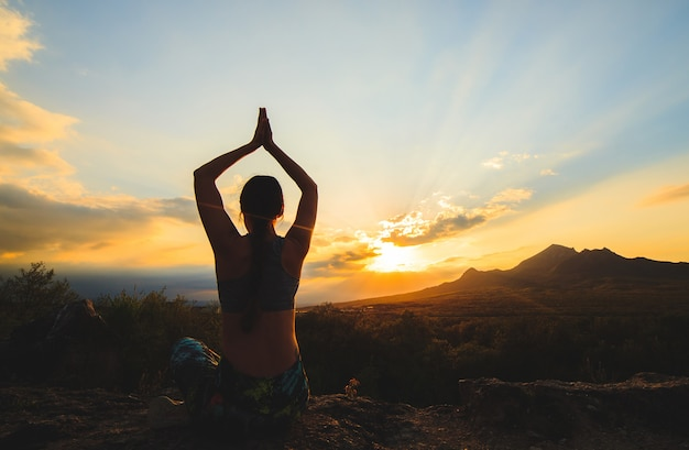 美しい山の場所で日没や日の出のヨガやピラティスを練習する若い女性。