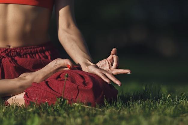 야외에서 요가 연습하는 젊은 여자. 여성 여름 도시 공원에서 야외 명상.