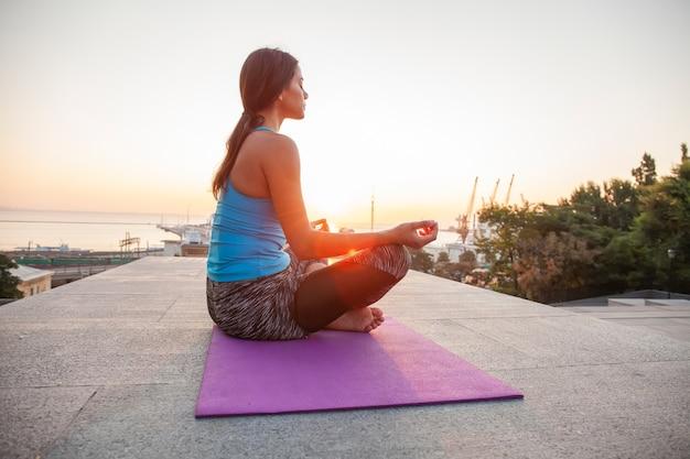 屋外でヨガを練習している若い女性。調和と瞑想の概念。健康的な生活様式