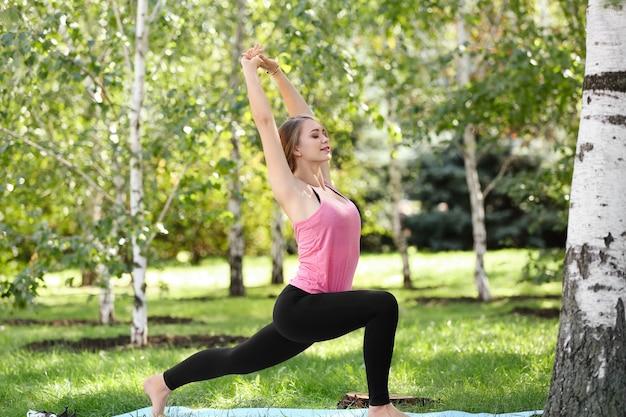 Молодая женщина упражнениями йоги на открытом воздухе