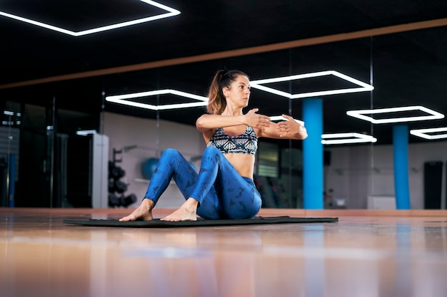 Young woman practicing yoga or pilates in a gym, doing stretching exercises.