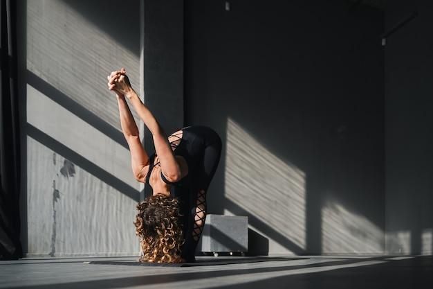 晴れた日に都会の背景でヨガのポーズを練習する若い女性