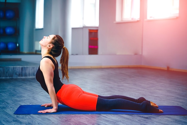 Молодая женщина упражнениями йоги в студии закрытый тренажерный зал. концепция здорового образа жизни.